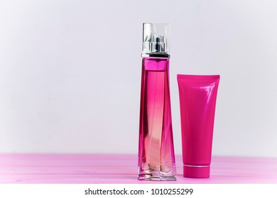 perfume bottle and cream on a pink wooden background