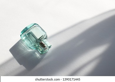 Perfume bottle or eau de toilette from transparent green glass on a white background with shadows