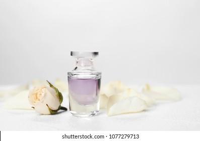 Perfume bottle and flower on table against light background