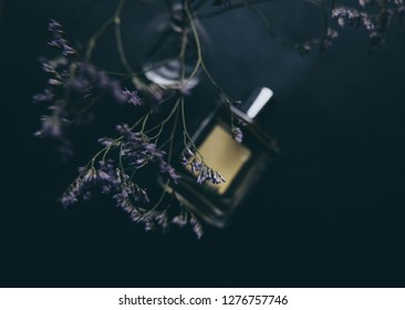 Perfume bottle with flowers fragrance mock up flat lay top view. Perfume background with bottle and purple flowers over sketchbook mockup. Spring, summer scent background for cards, wedding, blogs.