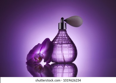 perfume bottle with fresh orchid flower on purple background