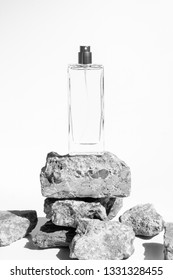 perfume bottle glass luxury packaging with stone rock concrete grunge on white background, aroma smell of cosmetic beauty container