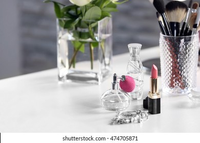 Perfume bottle with lipstick on light dressing table