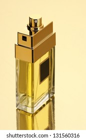 Perfume bottle on gold background with reflection.