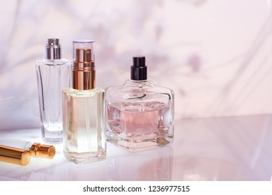 Perfume bottle on a light pink floral background. Selective focus. Perfumery collection, cosmetics