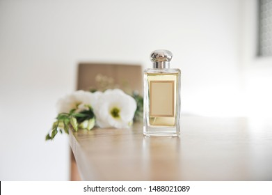 Perfume bottle on light wooden table.