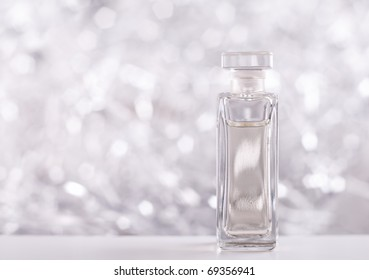 Perfume bottle on sparkling background