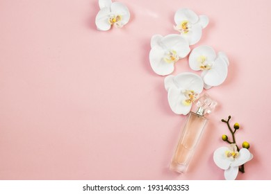 Perfume bottle, orchid flowers on pink background. Flat lay. copy space. Beautiful composition with perfume and flowers. Perfumery cosmetics, toilet water fragrance collection.