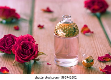 perfume bottle and pink roses on wooden table
