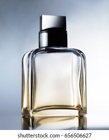 Perfume bottle and reflection on gray background