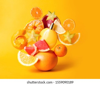 Perfume bottle with refreshing fruity smell between fresh fruits on yellow background