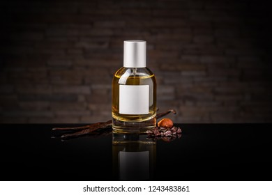 Perfume bottle and vanilla pods on dark background