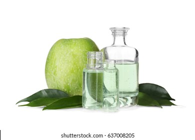 Perfume bottles and apple on white background