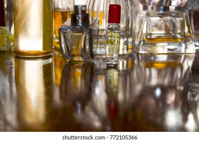 perfume bottles in back-lit on a wooden background and reflections of light