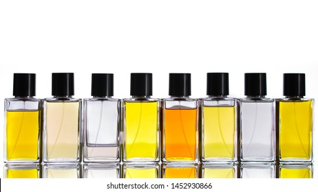 Perfume bottles, cologne, eau de parfum, fragrance for man and woman. A lot of bottle with aromatic colored liquid, panoramic view with reflection on white perfect isolated background