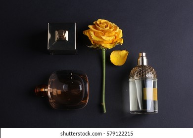 Perfume bottles with dry rose flower on black background