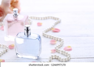 Perfume bottles with flower petals and beads on wooden table