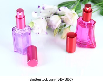 Perfume in bottles and flowers isolated on white
