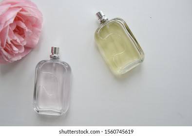 Perfume bottles and flowers on white background, top view. Flat lay arrangement with space for text.