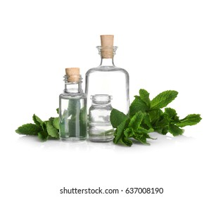Perfume bottles and fresh mint on white background