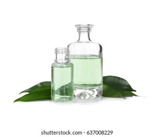 Perfume bottles and green leaves on white background