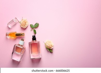 Perfume bottles on pink background, top view