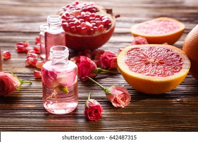 Perfume bottles, roses and fresh fruits on wooden table