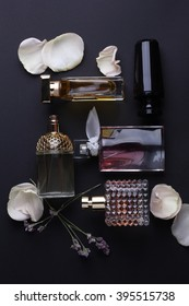 perfume bottles surrounded by flower on black background.