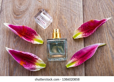Perfume bottles surrounded by lily petals. Eau de toilette. Eau de parfum. Parfum with flowers on wooden background.