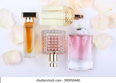 perfume bottles surrounded by rose flower (rose petals).