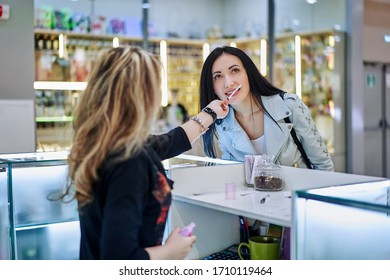 Perfume boutique, the seller offers a perfume sampler to a young woman in elegant clothes.