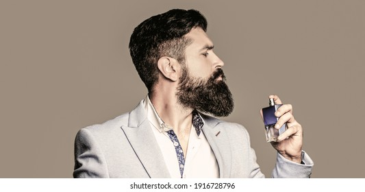 Perfume or cologne bottle and perfumery, cosmetics, scent cologne bottle, male holding cologne. Masculine perfume, bearded man in a suit. Masculine perfume, bearded man in a suit. - Shutterstock ID 1916728796