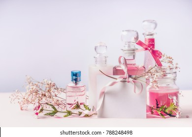 Perfume and cosmetics fleeting scents . Composition of bottles with flowers and blank greeting card with ribbon, front view. Beauty concept