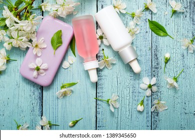 perfume droppers and soap with cherry flowers on old blue wood table