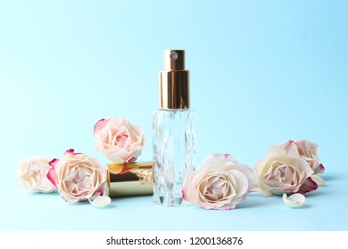 perfume and flowers on a colored background.