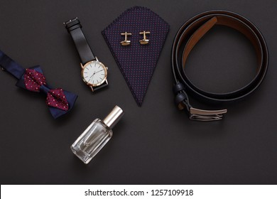 Perfume for men, bow tie, watch with a black leather strap, handkerchief with cufflinks and leather belt with metal buckle on black background. Accessories for men. Top view.