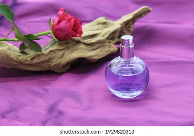 perfume mock up bottle on the purple draped fabric, pink rose on the driftwood nearby. beauty fragrant product mockup, minimalist concept