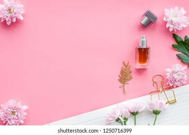 Perfume on feminine desk. Women's accessories. Perfume near notebook for dairy among flowers on pink background top view space for text