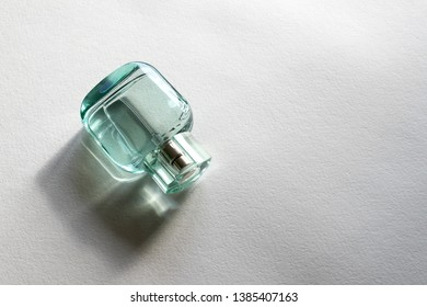 Perfume spray bottle made of transparent green glass on white background with copy space for your text, blank
