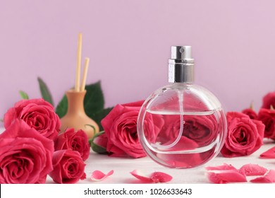 Perfume in spray bottle with pink roses flowers and incense sticks. Lilac tones background, aromatherapy set