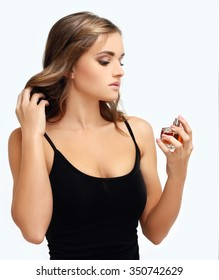 Perfume. Young girl smelling aroma with pleasure
