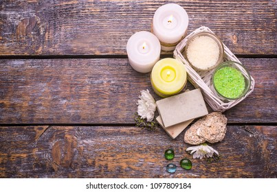 Perfumed salt white and green, scented candles, natural soap - spa treatment set with flowers on a wooden background, place for text. Top view.