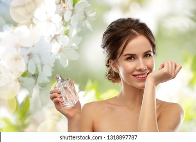 perfumery, beauty and luxury concept - happy smiling young woman smelling perfume from her wrist over natural spring cherry blossom background