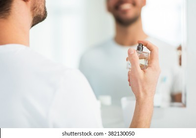 perfumery, beauty and people concept - close up of happy smiling young man with perfume looking to mirror using scent at bathroom