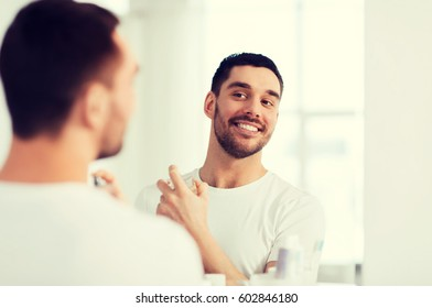 perfumery, beauty and people concept - happy smiling young man with perfume looking to mirror using scent at bathroom