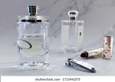 Perfumes in bottles, nail clipper and lipstick. Women beauty and care products set in a grey marble background.