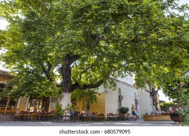 PERGAMON, TURKEY - JUNE, 25, 2017: People drink tea in the shadow of old plane tree, Izmir, Bergama