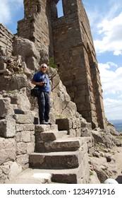 PERGAMUM, TURKEY - May 24, 2014 - Tourists explore the steeply sloping ruins of the Greek theater at  Pergamum above Bergama, Turkey