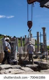 PERGE, TURKEY - JUN 2, 2014 - Workers use modern equipment to restore ancient columns in  Perge,  Turkey