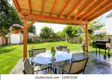 Pergola with patio area. Glass top table with chairs, fire pit and barbecue